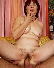 Redheaded granny shows off her hairy snatch and takes dick inside it