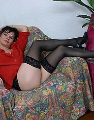 A mature brunette in black stockings poses and then gets fucked