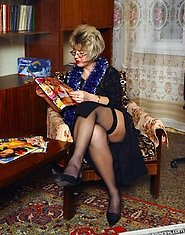 A horny granny touches herself when readying porn magazine