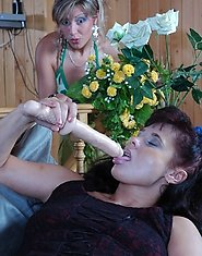 Mischievous girlie takes out her strap-on to massage a ripe pussy of a milf